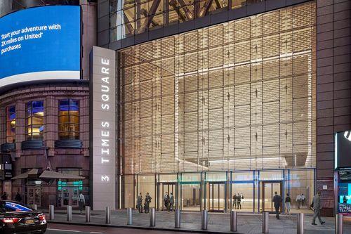 Рендеринг показывает обновленную площадь 3 Times Square с новым трехуровневым вестибюлем со стеклянными стенами и скульптурным фасадом, который будет рассеивать яркие огни района.